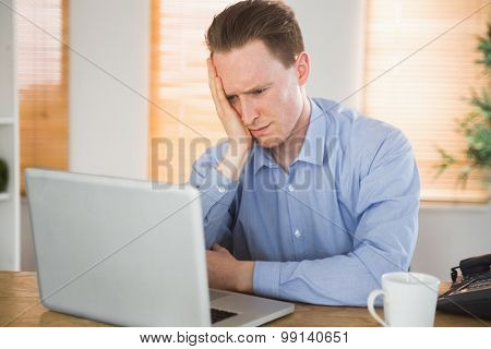 Fearful businessman looking at his laptop in the office