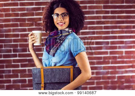 Portrait of smiling attractive hipster with felt bag and coffee against red brick background