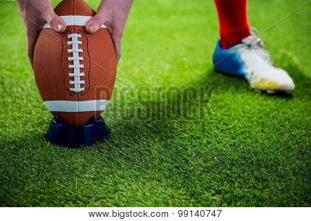 American football player preparing for a drop kick on american football field