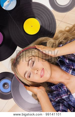A beautiful woman with headphones lying against vinyl