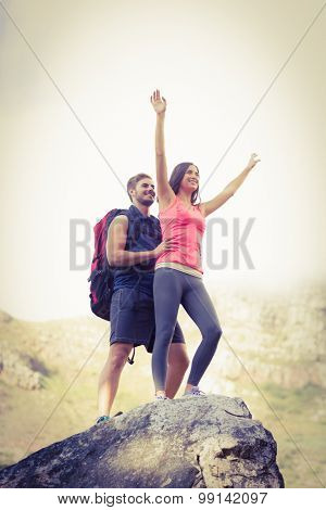 Young happy joggers posing on rock in the nature