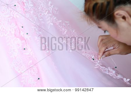 Woman Embroidering Pink Wedding Dress