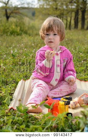 Girl Playing With Dolls In The Meadow