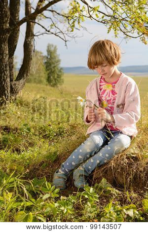 The Girl With Short Blond Hair Sitting On The Grass