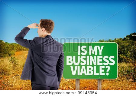 Wear view of businessman looking away against green road sign by mountain trail