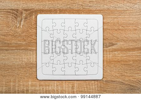 Blank Jigsaw Puzzle On Wooden Table