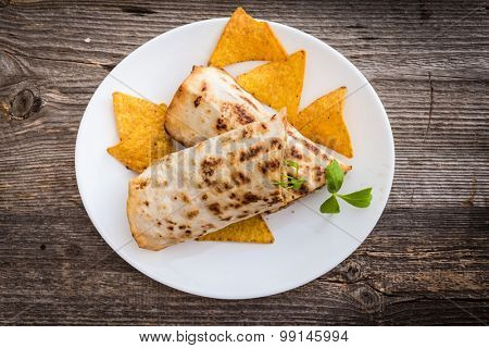 burrito with chips on a plate on a wooden background