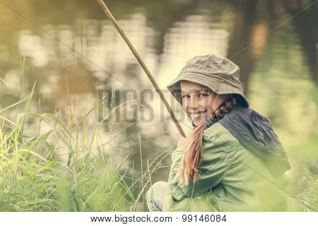 little fisher girl smiles sitting near a river with a rod