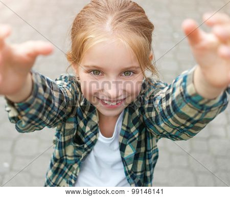 pretty little girl with arms up to reach something