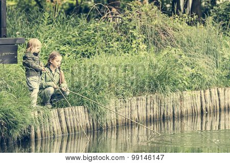 two little fisher girls with rods on a river bank