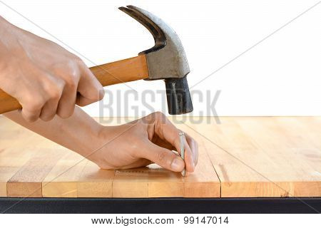 Hand Hammering A Nail On Wood Table Top