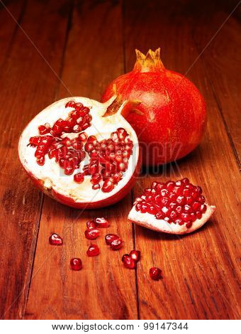 juicy pomegranate open on wood board. Filtered image: warm cross processed vintage effect.