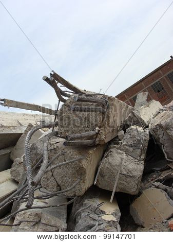Large Concrete Chunks With Twisted Metal And Industrial Building