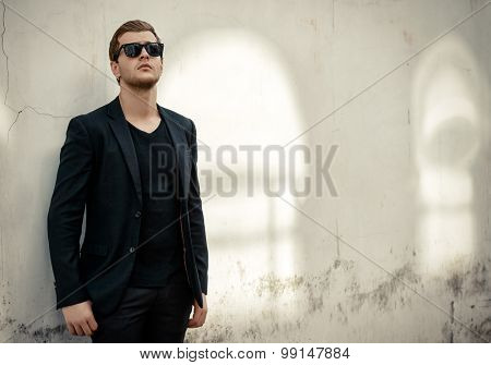 Handsome elegant man posing on a city street. Fashion shot. Business man outdoor.