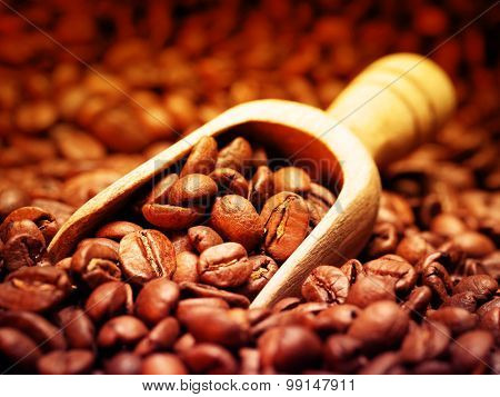 Closeup of coffee beans with wooden scoop. Filtered image: warm cross processed vintage effect.