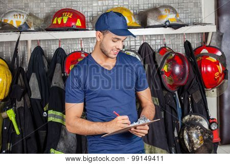 Young male firefighter writing on clipboard at fire station