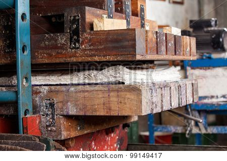 Closeup of papers in wooden press machine at factory
