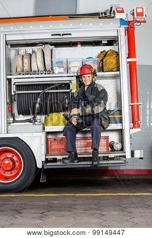 Portrait of happy fireman holding mug while sitting in truck at fire station