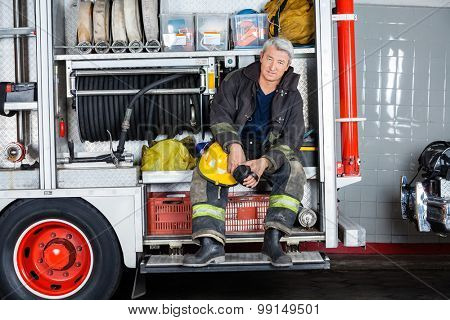 Full length portrait of confident fireman sitting in truck at fire station
