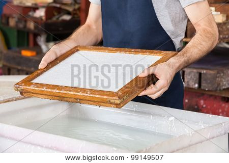 Midsection of male worker holding mold over pulp and water mixture at paper factory