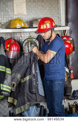 Young male firefighter wearing uniform at fire station