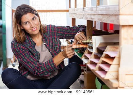 Portrait of smiling mid adult female customer choosing papers from shelf in store