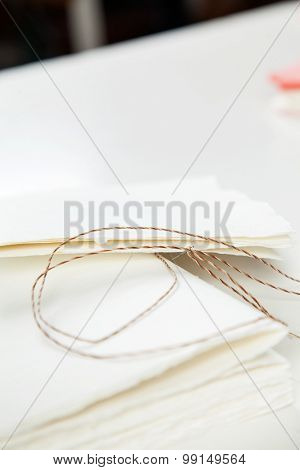 Closeup of thread and notepad papers on table