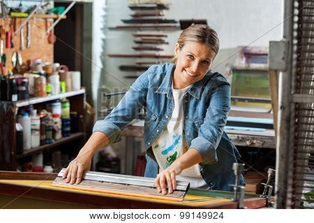 Portrait of smiling mid adult female worker using squeegee in factory