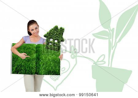 Woman pointing lawn book against house shape made of leaves