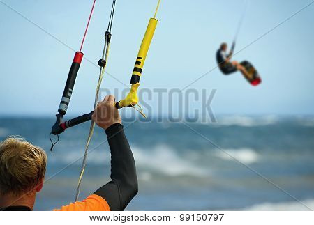 A young man kitesurfer ready for kite surfing rides in blue sea