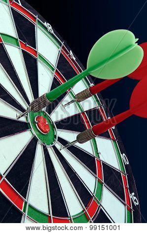 Darts In A Target For Darts Against A Dark Background.