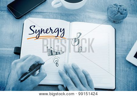 The word synergy and man writing notes on diary against business graphs