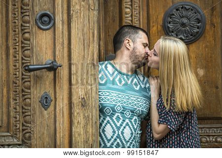 Young couple kissing while standing next to an ancient doors.
