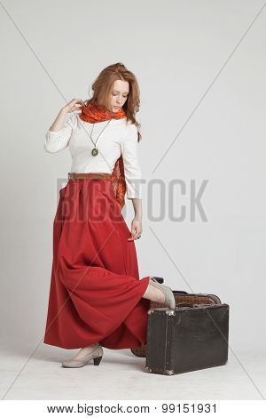 Young woman in vintage red skirt with suitcases