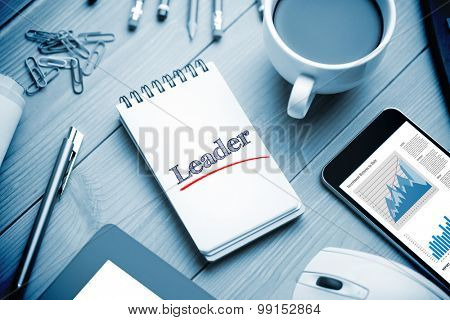 The word leader and business graphs against notepad on desk