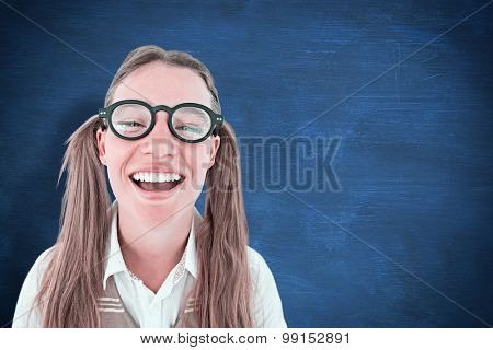 Female geeky hipster smiling at camera against blue chalkboard