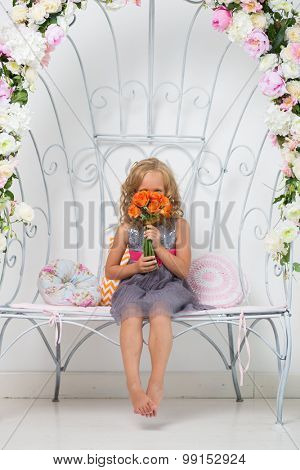 pretty teen girl sitting in the white room interior with flowers
