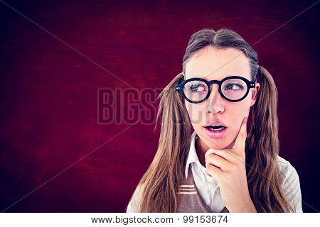 Female geeky hipster looking confused against desk