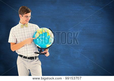 Geeky hipster holding a globe smiling at camera against blue chalkboard