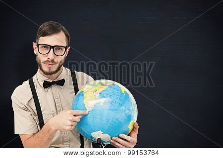Geeky hipster holding a globe against blackboard