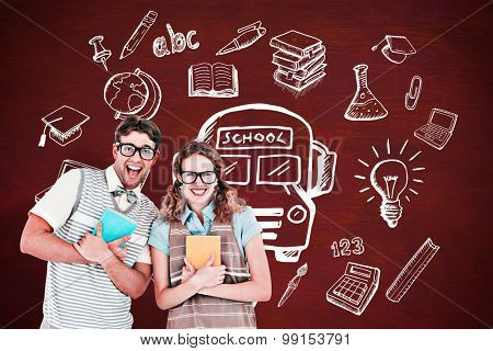 geeky hipster couple holding books and smiling at camera against desk