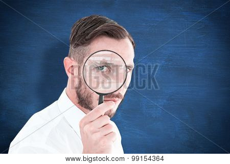Geeky businessman looking through magnifying glass against blue chalkboard