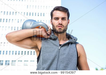 Portrait of handsome athlete holding kettle bell in the city