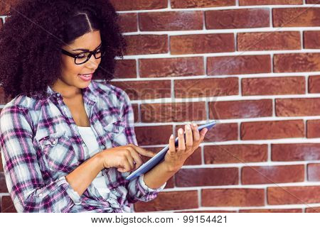 Attractive hipster leaning on wall and using tablet against red brick background