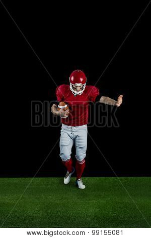 American football player wrestling through and protecting football on american football field