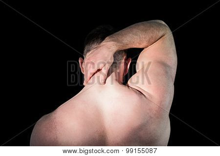 Strong bodybuilder with painful neck on black background