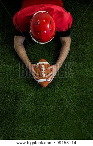 American football player reaching football on american football field