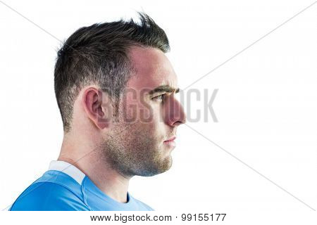 Tough rugby player looking away on white background