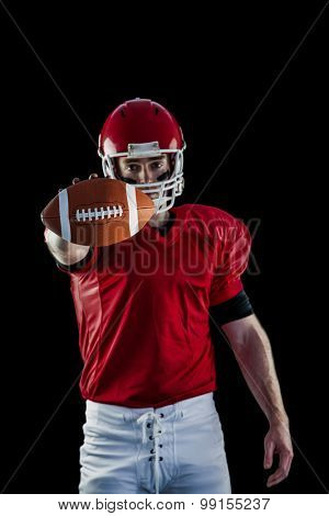 Portrait of american football player showing football to camera against black background