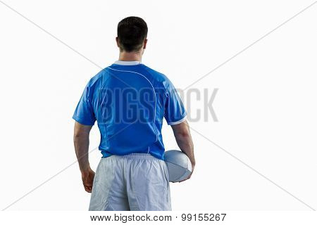 Back turned rugby player holding a rugby ball
